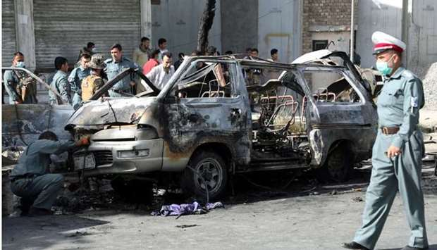 Afghan security forces inspect the wreckage of a passenger van after a blast in Kabul, Afghanistan o