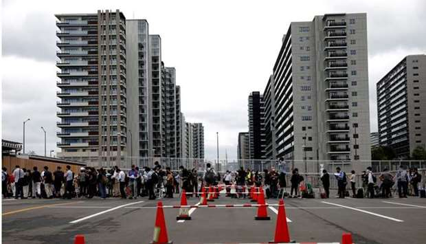 Journalists stand in a line to enter the village plaza of the Tokyo 2020 Olympic and Paralympic Vill