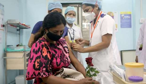 A healthcare worker holding a rose receives an AstraZeneca's Covishield vaccine, during the coronavi