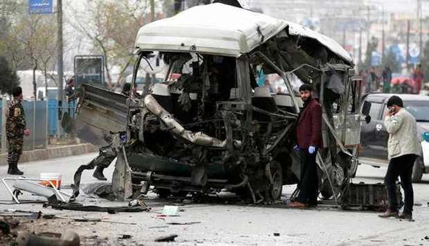 Afghan officials inspect a damaged minibus after a blast in Kabul (file photo)
