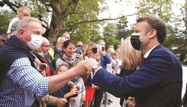 French President Emmanuel Macron greets voters at a polling station during the first round of region