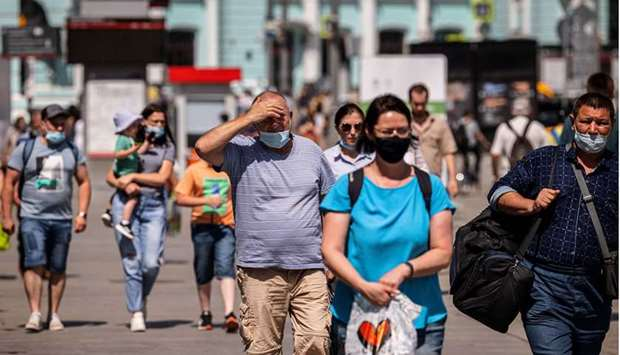 People wearing face masks walk down a street in Moscow