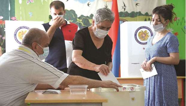People cast their ballots at a polling station during early parliamentary elections in Yerevan yeste