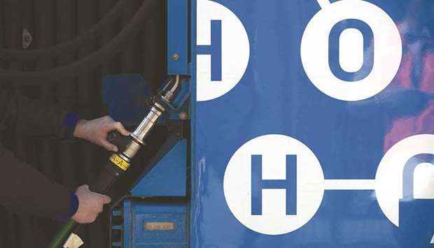 A worker refuels a hydrogen fuel cell-powered prototype railway train at a refuelling station in Sal