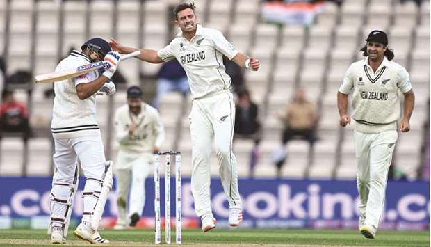 New Zealand's Tim Southee (C) celebrates dismissing India's Rohit Sharma (L) for 30 runs on the fift