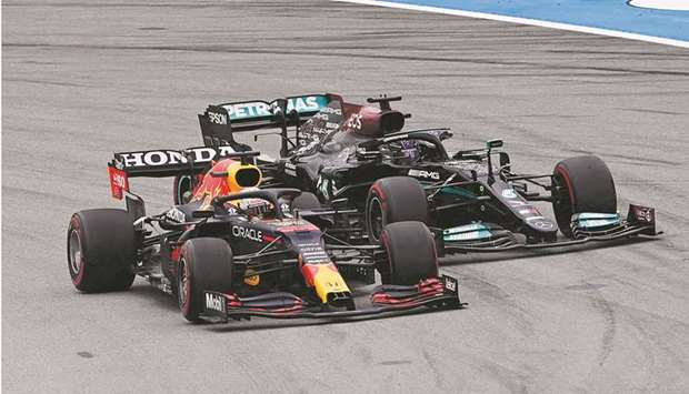 Red Bull's Dutch driver Max Verstappen overtakes Mercedes' British driver Lewis Hamilton at the star