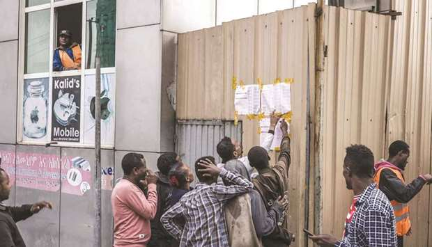 Ethiopian voters look at tallies posted outside a polling station in Addis Ababa, yesterday.