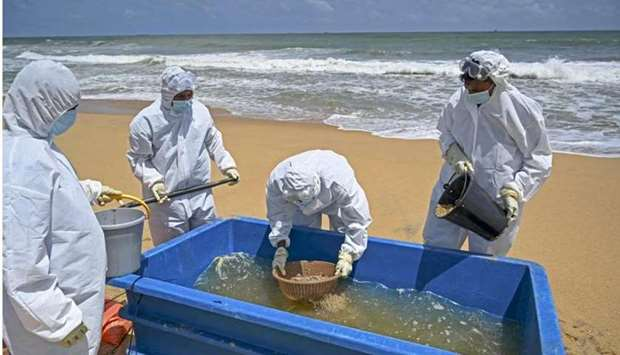 Members of the Sri Lankan Navy work to remove debris washed ashore from the Singapore-registered con