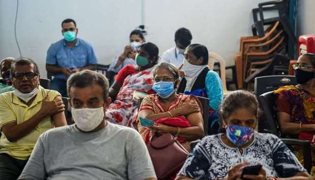 People wait in an observation area after getting inoculated with a dose of the Covishield AstraZenec