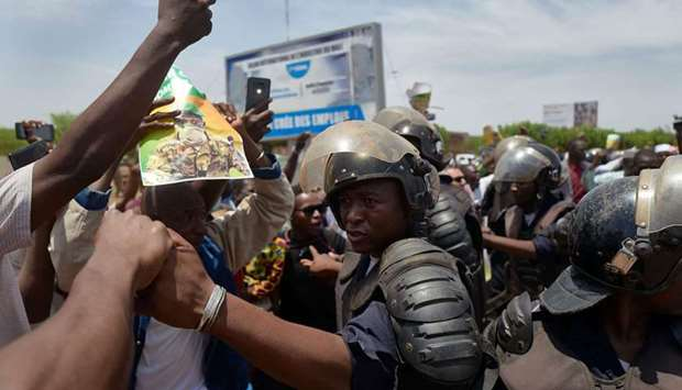 Malian riot police keep supporters away from the vehicle of new President of Mali's transitional gov