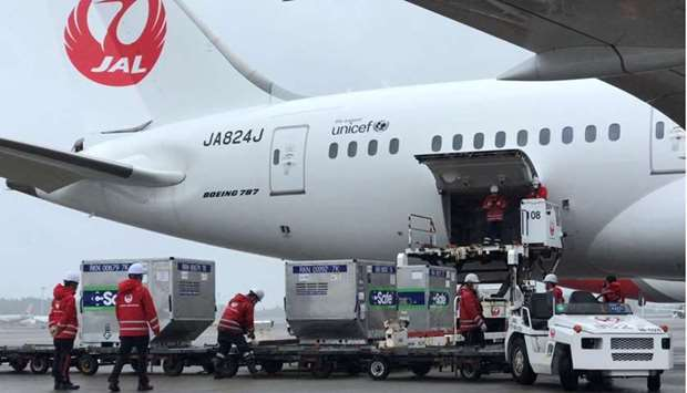 Workers load vaccines against the coronavirus disease (Covid-19) to an airplane before the plane, he