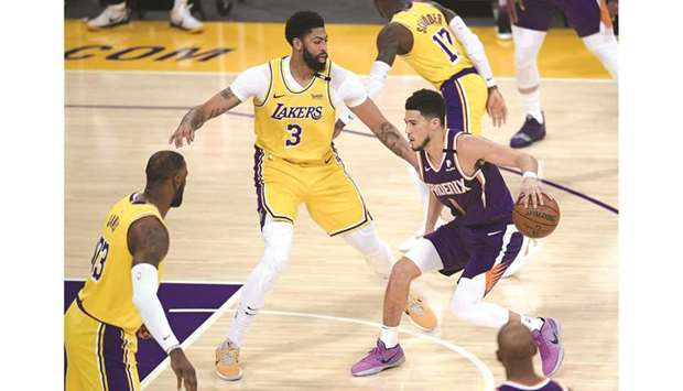 Devin Booker (right) of the Phoenix Suns dribbles in front of Anthony Davis (centre) and LeBron Jame