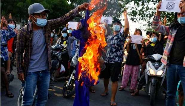 Protesters against Myanmar's junta burn the flag of the Association of Southeast Asian Nations (ASEA