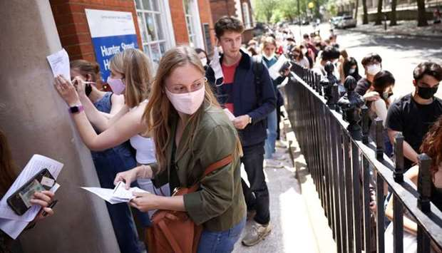 People fill in paperwork while queueing outside a vaccination centre for young people and students a