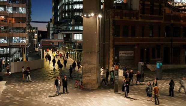 People walk through the Central Business District (CBD) at dusk in Sydney, Australia