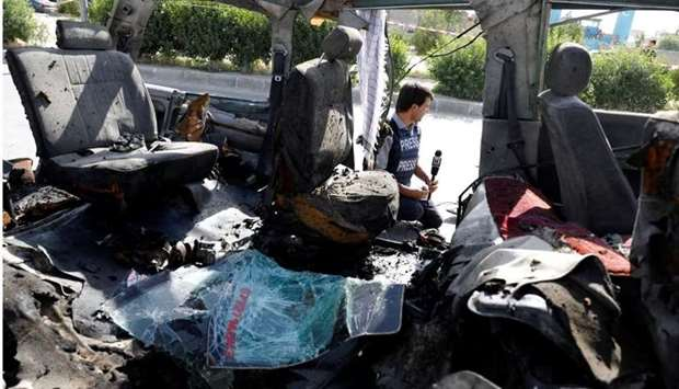 An Afghan journalist reports next to a damaged van after a blast on June 3 in Kabul. Reuters