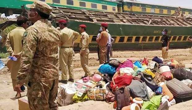 Security personnel stand at the site of a train accident in Daharki area of the northern Sindh provi