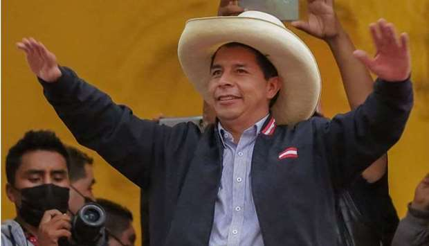 Peruvian presidential candidate Pedro Castillo gestures at supporters from a balcony of his party's