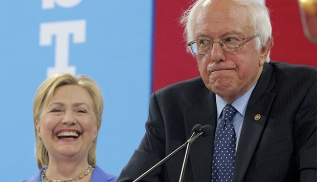 Democratic US presidential candidate Hillary Clinton smiles as Senator Bernie Sanders pauses while e