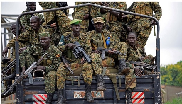 Uganda People's Defence Forces (UPDF) soldiers ride atop their military truck enroute to evacuate th