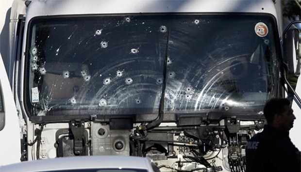 Bullet impacts are seen on the heavy truck the day after it ran into a crowd at high speed in Nice