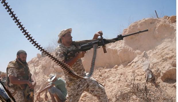 A fighter of Libyan forces allied with the UN-backed government fires a weapon during a battle with