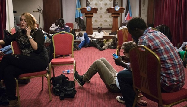 Journalists sit inside the conference room as artillery fire broke out near the presidential palace