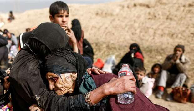 Khatla Ali Abdullah, 90, is embraced as she flees her home as Iraqi forces battle with Islamic State