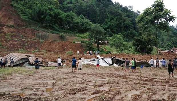 Indian villagers look on during a rescue operation at the site of a landslide in Laptap village