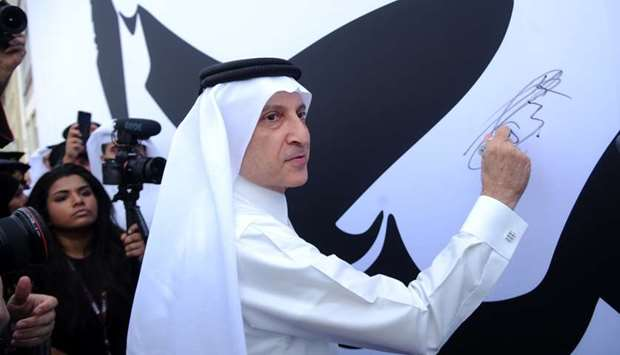 Qatar Airways Group Chief Executive Akbar al-Baker signs on the giant canvas, which displays the ico