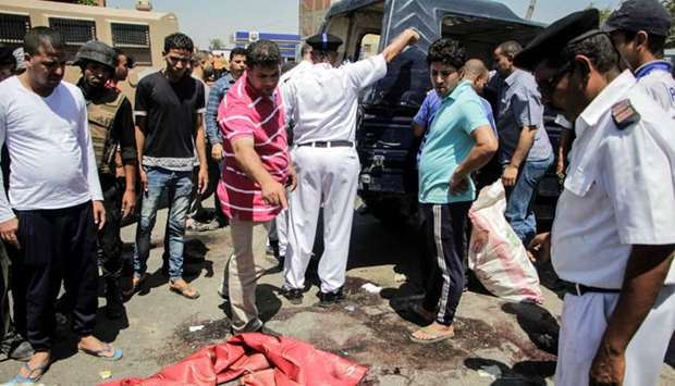 Egyptian policemen inspect the scene of an attack which left five of their colleagues killed in a sh