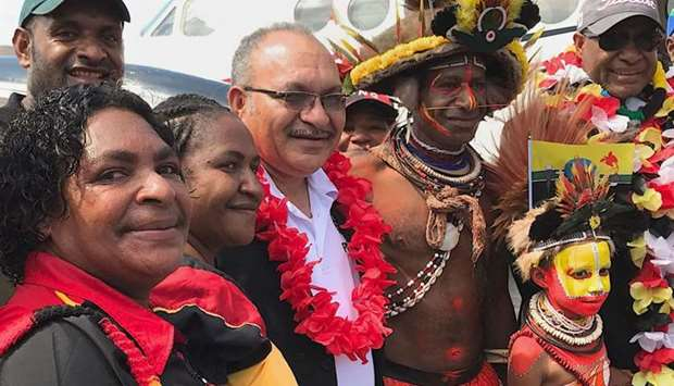 Papua New Guinea Prime Minister Peter O'Neill (C) posing as he is welcomed as he returns to Port Mor