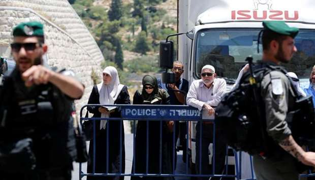 Palestinians stand next to a police barricade as they wait for the compound known to Muslims as Nobl