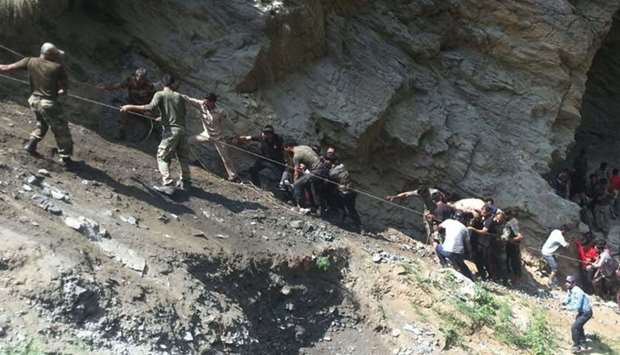 Indian police personnel and locals carry injured and dead from the site of a bus accident in Ramban