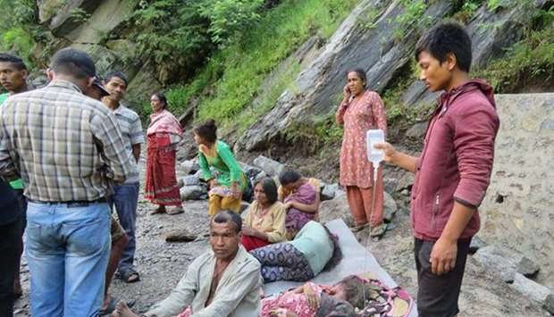 People wait for relief after being displaced by flood in Khani Khola and other rivulets in Khimti Ba