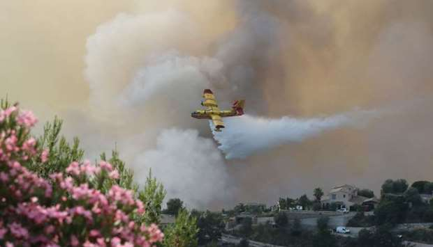 A Canadair airplane drops water over a fire near houses in Castagniers, near Nice