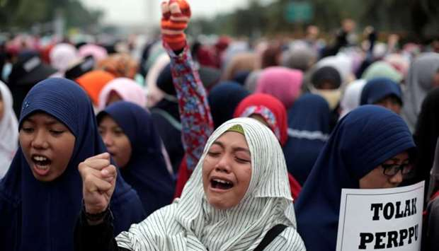 A group of Indonesian Islamists shout slogans during a protest against the President Joko Widodo's d