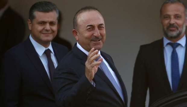 Turkey's Foreign Minister Mevlut Cavusoglu greets journalists during a visit in the Turkish Cypriot