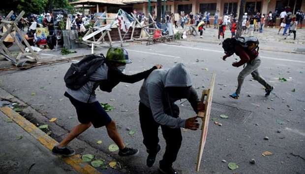 Demonstrators clash with riot security forces during a strike called to protest against Venezuelan P