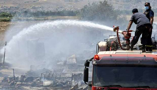 Civil defence members put out fire at a camp for Syrian refugees near the town of Qab Elias, in Leba