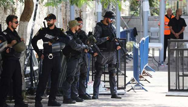 Israeli police officers stand guard next to recently installed metal detectors at an entrance to the