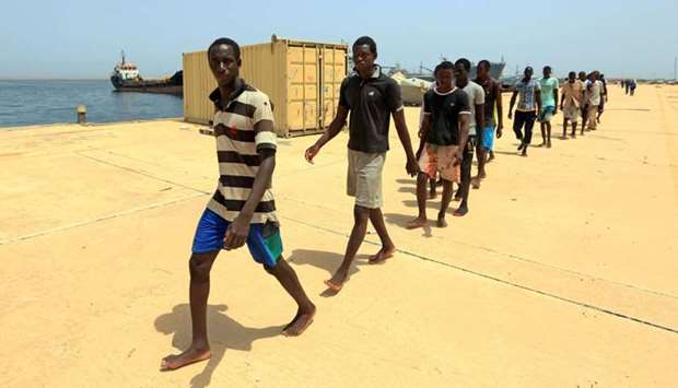 Illegal migrants from Africa, walk at a port in Tripoli prior to being taken to a naval base after t