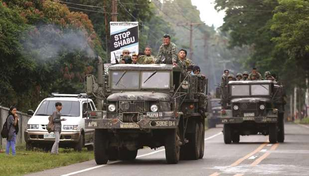 Trucks carrying members of Philippine Marines pass by a town on their way to Marawi city.