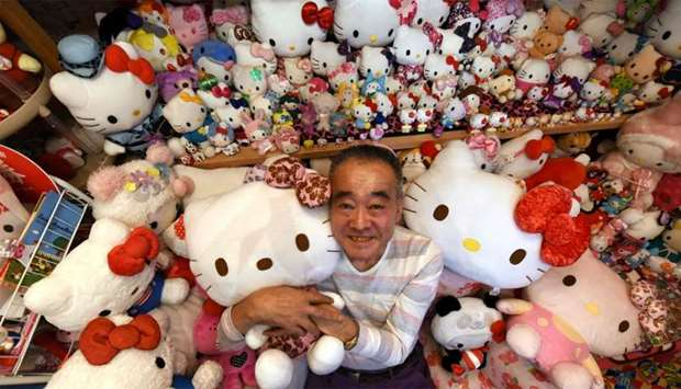 Retired Japanese police officer Masao Gunji posing with his Hello Kitty collection