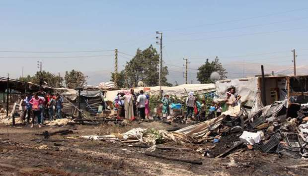 Syrian refugees look at the damage after a fire engulfed part of the Tel al-Sarhoun refugee camp