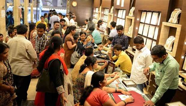 Indian customers gather to purchase gold items in a jewellery shop