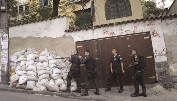 Policemen take up position after a resident was killed during a violent clash during an operation ag