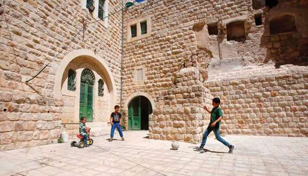 Palestinian children play with a ball outside their house in the old town of the West Bank city of H
