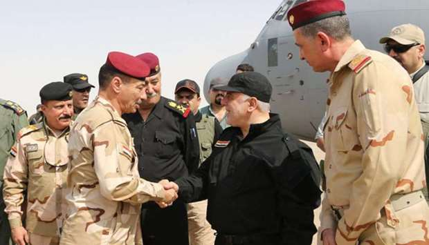 Iraqi Prime Minister Haider al-Abadi (C-R) shaking hands with army officers upon his arrival in Mosu