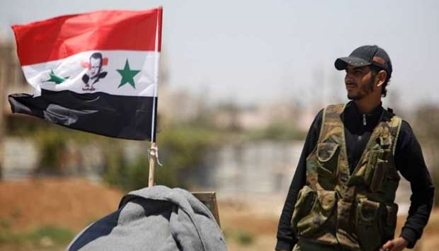 A Syrian army soldier stands next to a Syrian flag in Umm al-Mayazen, in the countryside of Deraa, S